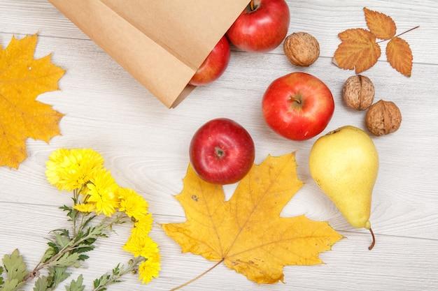 Rijpe gele peer, walnoten, rode appels met papieren zak en bloemen op houten bureau. gezonde biologische voeding. herfst thema. bovenaanzicht.