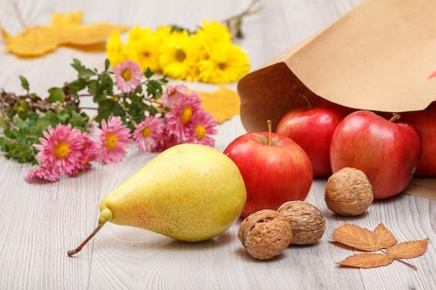Rijpe gele peer, walnoten, rode appels met papieren zak en bloemen op houten bureau. gezonde biologische voeding. herfst thema.