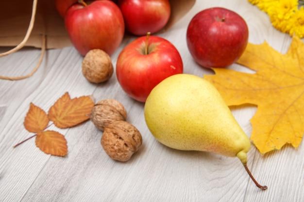Rijpe gele peer, walnoten, rode appels met papieren zak en droge bladeren op houten bureau. gezonde biologische voeding. herfst thema.