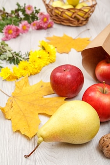 Rijpe gele peer, walnoten, rode appels met papieren zak, rieten mand en bloemen op houten bureau. gezonde biologische voeding. herfst thema.