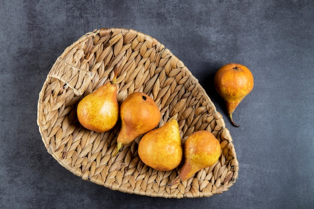 Rijpe gele peren in een rieten mand met palmbladeren op een grijze stenen tafel