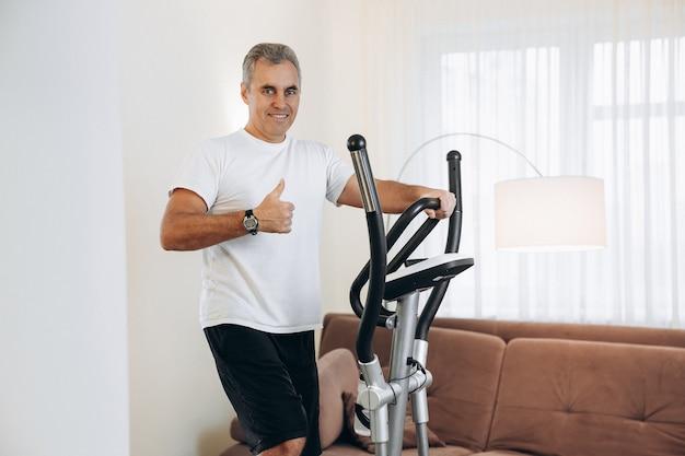 Rijpe gelukkige mens die op elliptische trainer oefent en omhoog duimen