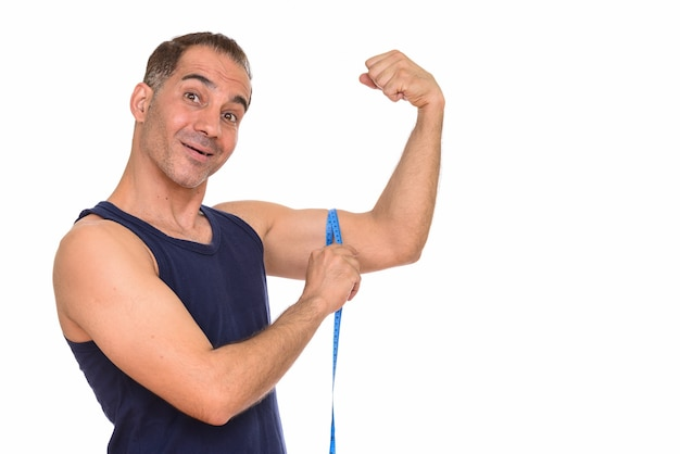 Rijpe gelukkige perzische mens die biceps met een meetlint meet