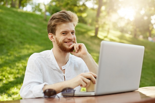Rijpe gember knappe man met laptopcomputer in het park