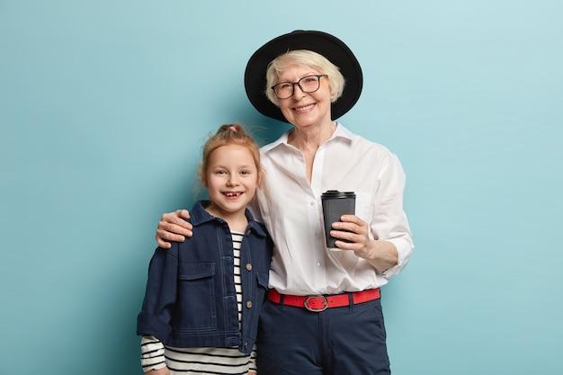 Rijpe, gerimpelde grootmoeder en haar kleindochter voor kleuters omhelzen elkaar en staan dicht bij elkaar, hebben een blije glimlach, drinken afhaalkoffie, hebben goede relaties. generatie concept