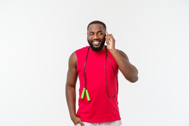 Rijpe geschikte afrikaanse amerikaanse mens die op mobiel spreekt en elastisch touw houdt.