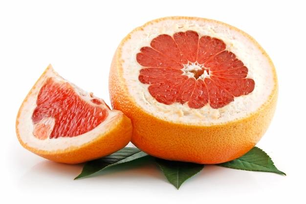 Rijpe gesneden grapefruit met bladeren geïsoleerd op wit