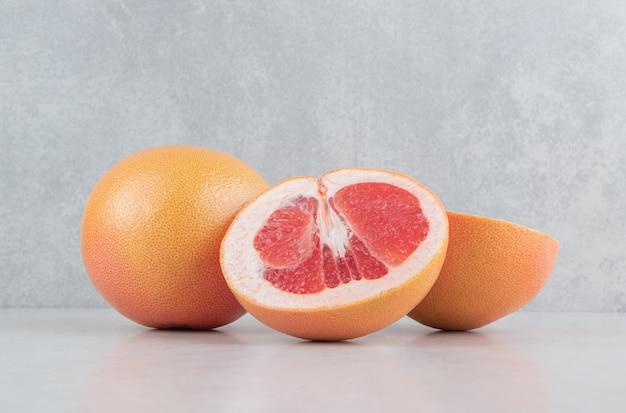 Rijpe gesneden grapefruits op stenen tafel.