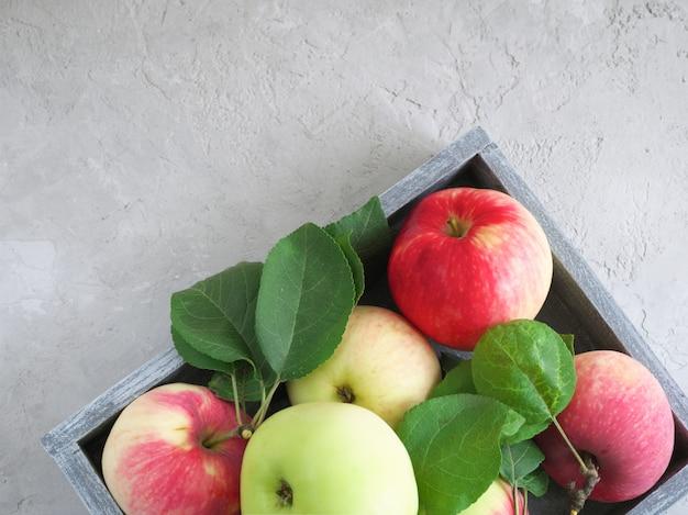 Rijpe, geurige rood-groene appels in een houten grijze doos op grijze stucwerk achtergrond