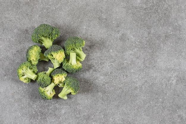Rijpe gezonde verse broccolis geplaatst op stenen tafel.