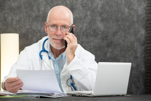 Rijpe glimlachende gebaarde arts die op telefoon spreekt
