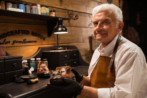 Rijpe glimlachende schoenmaker die in workshop schoenen maakt