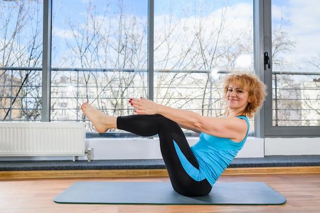 Rijpe glimlachende sportieve vrouw in vrijetijdskleding zit op mat en lichaamsspieren opwarmen