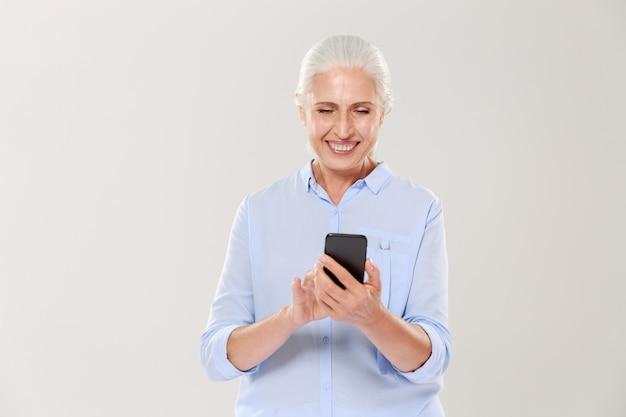 Rijpe glimlachende vrouw die geïsoleerde smartphone gebruiken