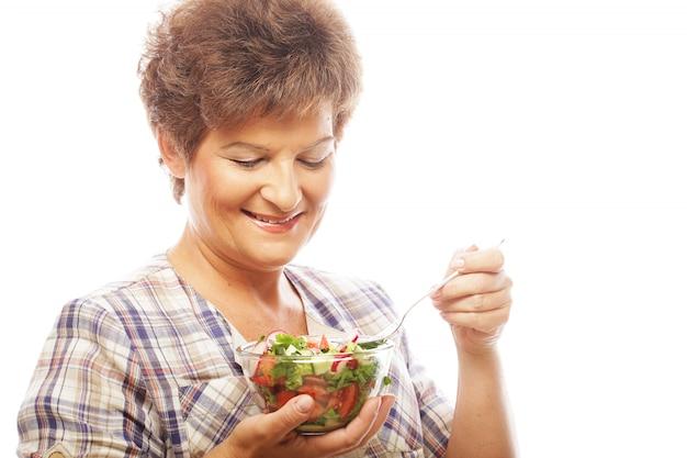 Rijpe glimlachende vrouw die salade eet