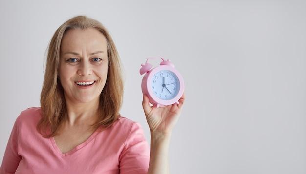 Rijpe glimlachende vrouw in een roze overhemd houdt een wekker, gelukkig kijkend naar de camera. foto op een grijze achtergrond met kopie ruimte.