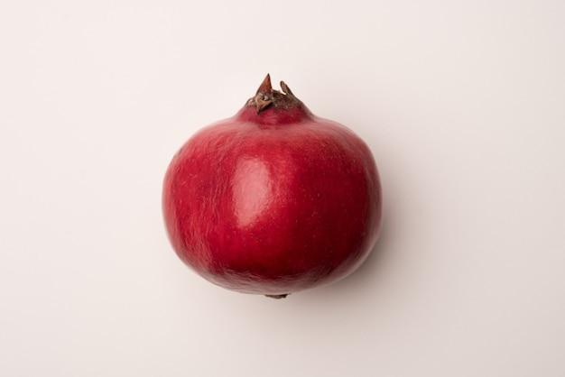Rijpe granaatappel die over wit wordt geïsoleerd