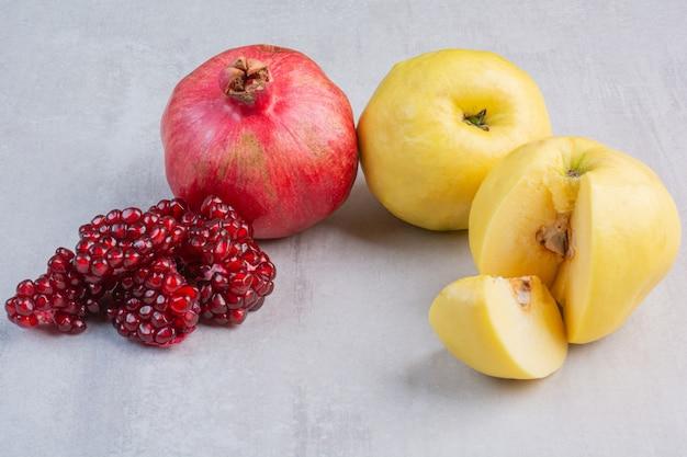 Rijpe granaatappel en appel, op het marmer.