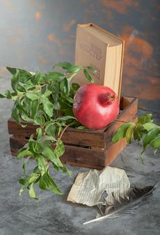 Rijpe granaatappel en boek in houten kist met bladeren en veren