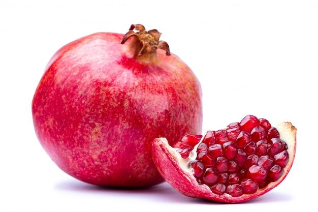 Rijpe granaatappel en het knippen weg met rode zaden die op witte achtergrond worden geïsoleerd