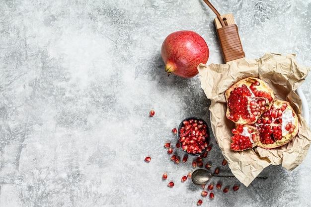 Rijpe granaatappel en zaden op een houten snijplank. biologisch fruit. grijze achtergrond. bovenaanzicht ruimte voor tekst