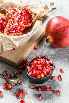 Rijpe granaatappel en zaden op een houten snijplank. biologisch fruit. grijze muur. bovenaanzicht