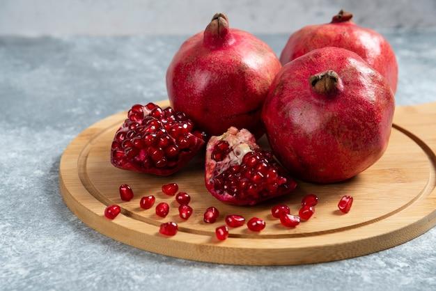 Rijpe granaatappel gesneden op een houten bord.