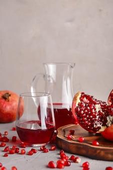 Rijpe granaatappels en glaswerk met sap op tafel