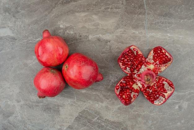 Rijpe granaatappels en zaden op marmeren tafel.