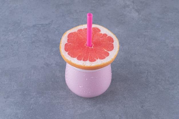 Rijpe grapefruit met glas sap op tafelblad weergave.