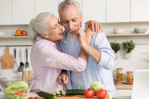 Rijpe grappige houdende van paarfamilie gebruikend laptop en kokende salade