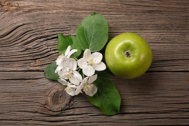 Rijpe groene appel met tak van witte bloemen op een houten tafel. bovenaanzicht met ruimte voor uw tekst.