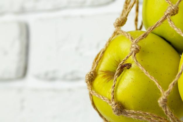 Rijpe groene appels in een lichte string zak, close-up