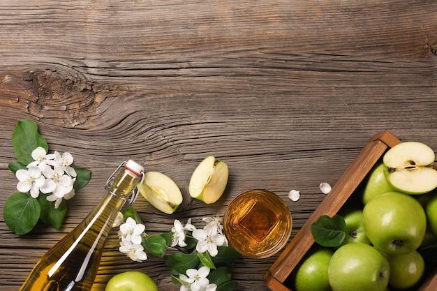 Rijpe groene appels in houten kist met tak van witte bloemen, glas en fles cider op een houten tafel. bovenaanzicht met ruimte voor uw tekst.