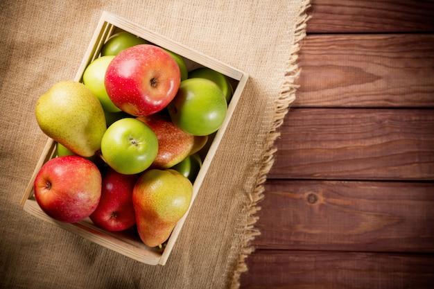 Rijpe groene en rode appels met peren in een houten doos