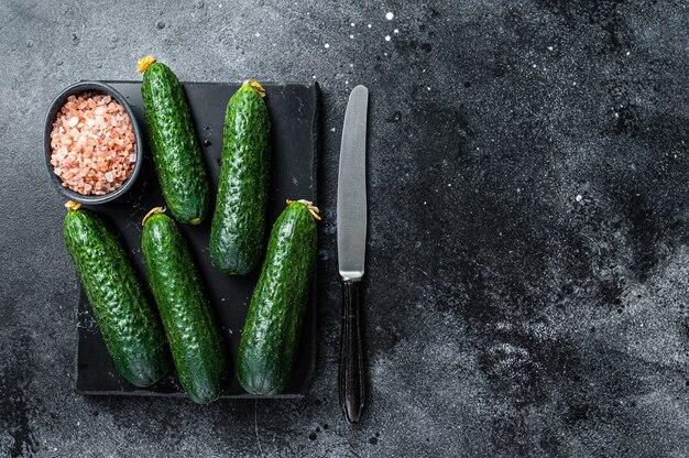 Rijpe groene komkommers op een marmeren bord. zwarte achtergrond. bovenaanzicht. ruimte kopiëren.