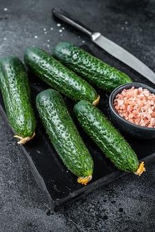 Rijpe groene komkommers op een marmeren bord. zwarte achtergrond. bovenaanzicht.