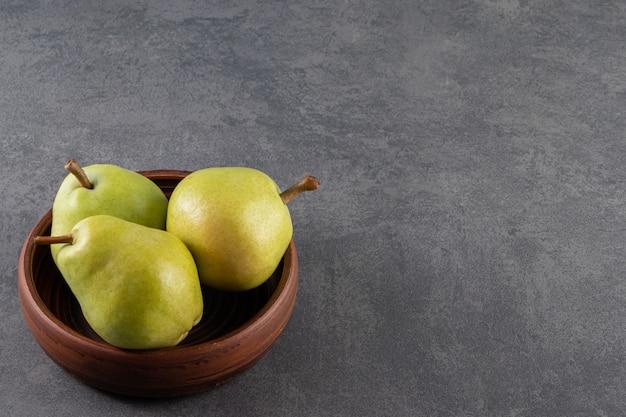 Rijpe groene peren in houten kom die op steen wordt geplaatst