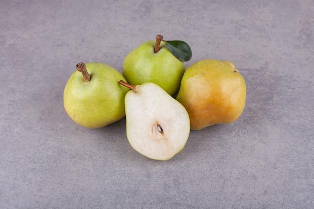 Rijpe groene peren met bladeren op een stenen oppervlak.