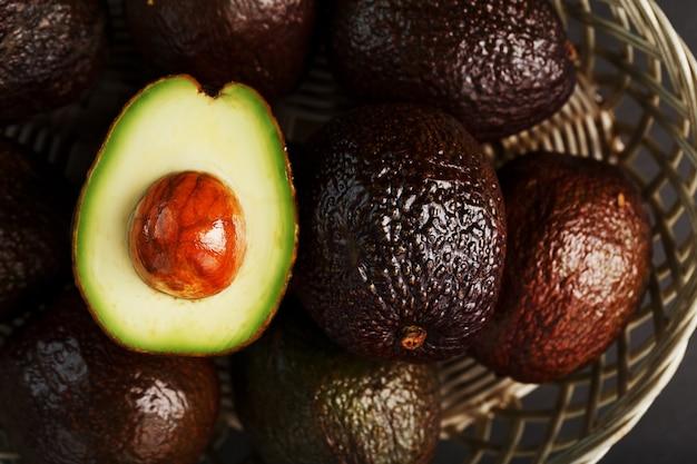Rijpe hass-avocado en een kuiltje in een mand op een zwart gestructureerd oppervlak