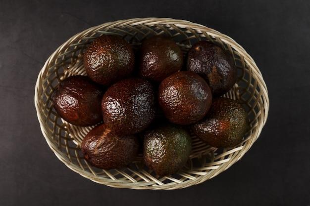 Rijpe hass-avocado in een mand op een zwart gestructureerd oppervlak