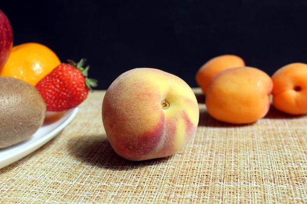 Rijpe heerlijke malse nectarine ligt op tafel naast een bord met fruit en bessen, op een zwarte muur. hard direct licht.