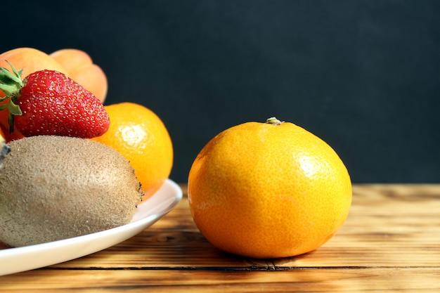Rijpe, heerlijke mandarijn ligt op tafel naast een bord met fruit en bessen op tafel, op een zwarte muur. hard direct licht.