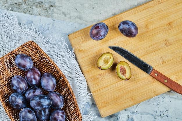 Rijpe hele en half gesneden pruimen op een houten bord. hoge kwaliteit foto