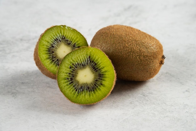 Rijpe hele kiwi's en halve kiwi's op wit.