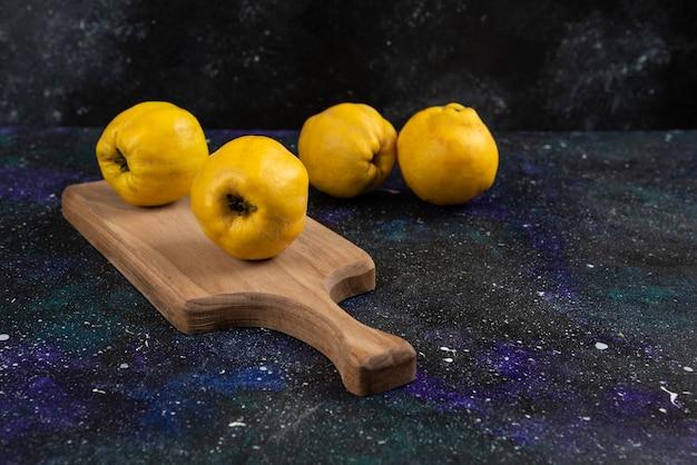 Rijpe hele kweepeervruchten op een houten bord en op een donkere tafel.