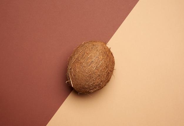 Rijpe hele ronde kokosnoot op een bruine achtergrond, bovenaanzicht