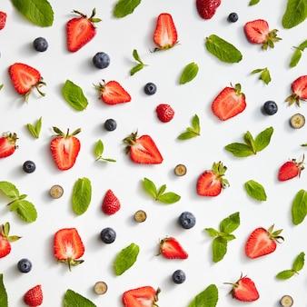 Rijpe helften van aardbeien, bosbessen en muntblaadjes