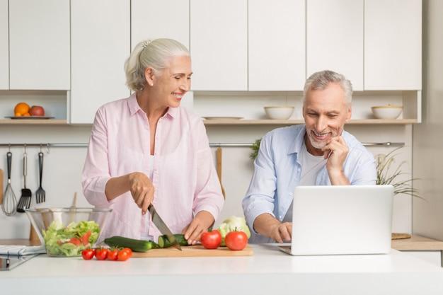 Rijpe houdende van paarfamilie gebruikend laptop en kokende salade