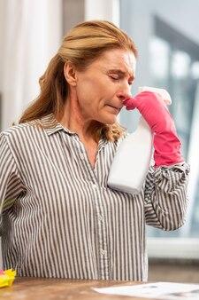 Rijpe huisvrouw die roze handschoenen draagt, zich ziek voelt en lijdt aan veel allergieën